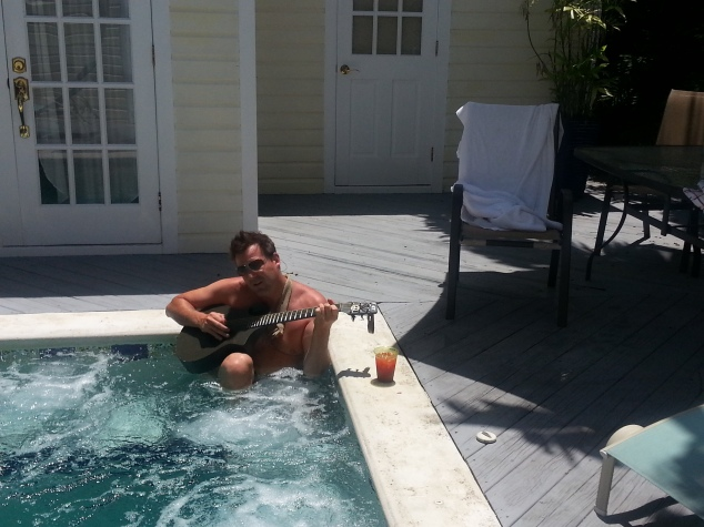 Travis playing guitar in the pool